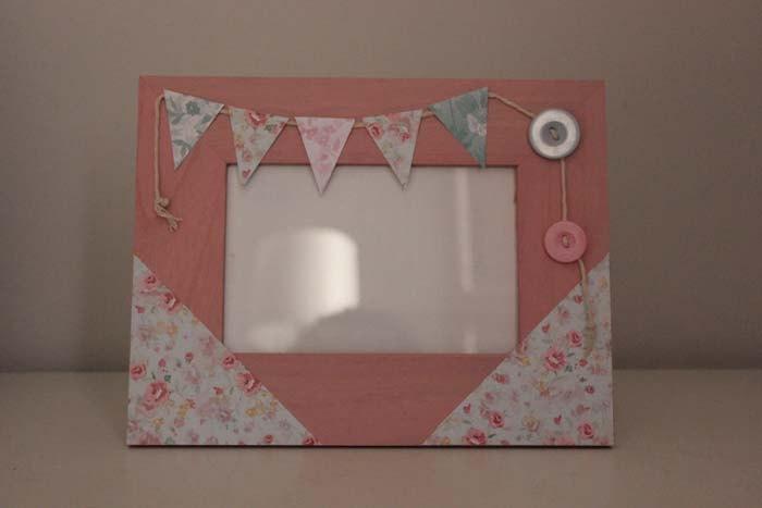 Marco de madera pintado a mano en color rosa y decorado con papeles y abalorios decorativos de scrapbooking. €20,00, via Etsy.