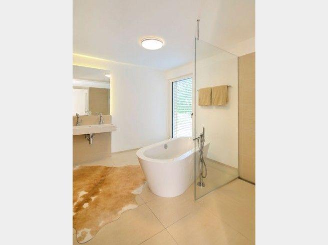 Badezimmer mit freistehender Badewanne und bodengleicher Dusche, was wünscht man sich mehr? Erdige Farbtöne verleihen dem Raum angenehme Wärme.