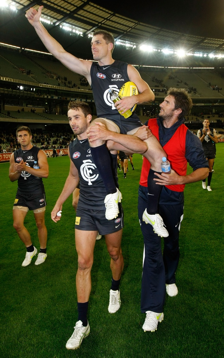 200 gamer Heath Scotland is carried from the field by Carlton teammates Andrew Walker and Jarrad Waite after the Round 1 match against the Tigers at the MCG in 2011.