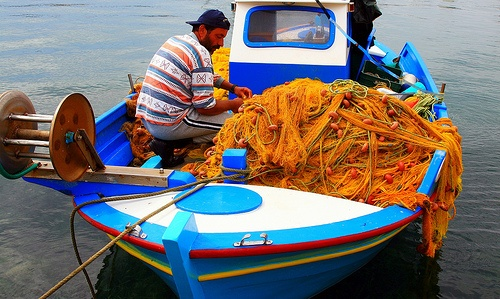 by Marite2007, via Flickr ~ Fisherman repairing fishing nets on board his fishing boat. Lipsi island, Dodecanese, Greece