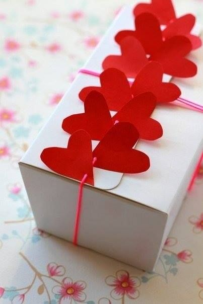 Gift Wrap - String embellishments like red hearts as a decorative touch for a plain gift box.
