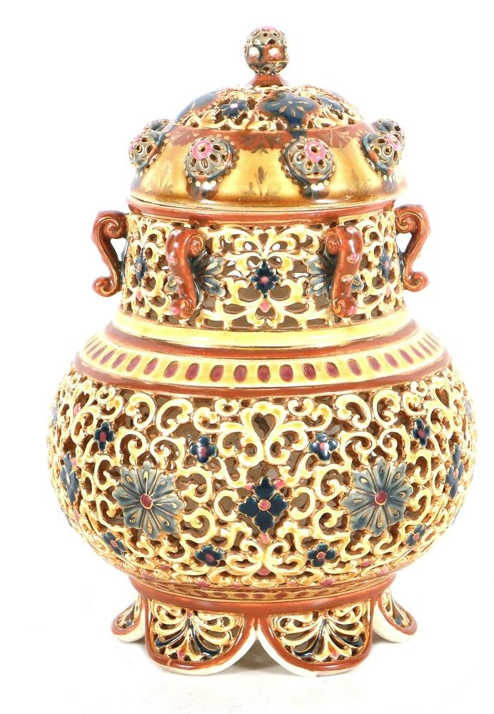 "Zsolnay ceramic lidded jar, Pécs, Hungary, ca. 1875-76. Hand painted with polychrome and gilt decoration. Highly reticulated lid and body with blue floral motif and acanthus scrolls around the neck. Impressed mark to the underside, ""ZSOLNAY, PECS, 1980."" 17/E400U"