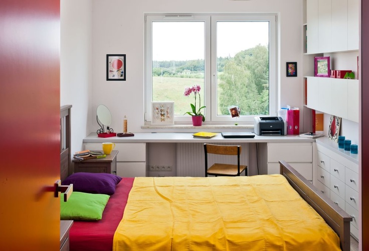Aranżacja sypialni dzięki dodatkom sprawia wrażenie wesołej i kolorowej. Na drugi rzut oka możemy jednak stwierdzić, że wszystkie meble w sypialni są białe, poza drewnianym łózkiem. Ciekawy strongprojekt sypialni/strong pozwolił urządzić w niej wygodne biuro. Miejsce do pracy w sypialni - porady.