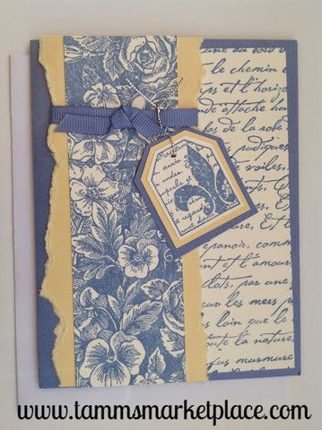 A Flor de Lis is centered on this pretty blue and yellow hand made card and appears as a gift tag tied to the matching blue ribbon. Layers of paper are arranged to make this unique card an original. I