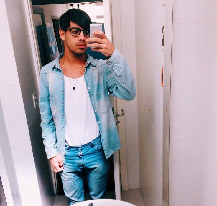 Menino, jovem, roupa masculina para o dia, casual, calça jeans clara, regata e camisa jean, colar masculino, óculos de grau hipster para homens. Cabelos com franja, cenário casual, selfie e iphone 5s