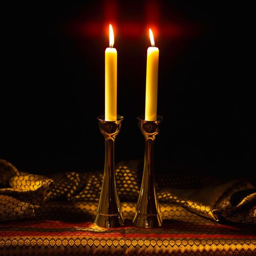 How did the ritual of Shabbat candle lighting come to be associated with women?