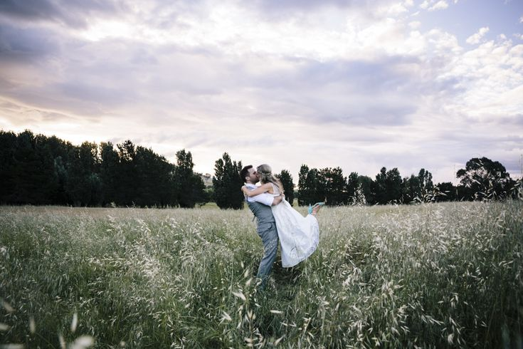 Groom picks up bride in long grassy field. Bride wears tea length wedding dress at Poachers Pantry ceremony and reception venue, country New South Wales