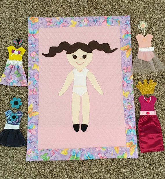 """Paper Doll Quilt Pattern. Complete instructions for making an adorable doll sized Paper Doll Quilt with interchangeable clothing, a pet dog and pet cat. Finished product measures 21 X 29 1/2. MATERIALS NEEDED: 1 Yard Double Faced, Pre-Quilted Fabric (Makes two 22""""x29.5"""" Quilts 1 Yard Fabric for quilt border (Makes two Paper Doll Quilts) Miscellaneous Felt Miscellaneous Fabric Miscellaneous Ribbon, Toole, Lace and embellishments for outfits and hair bows Matching Tread Embroidery Floss f..."""