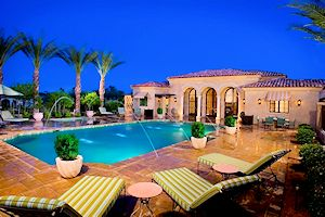 Sparking pool with shooting water fountains and palm trees in the yard.