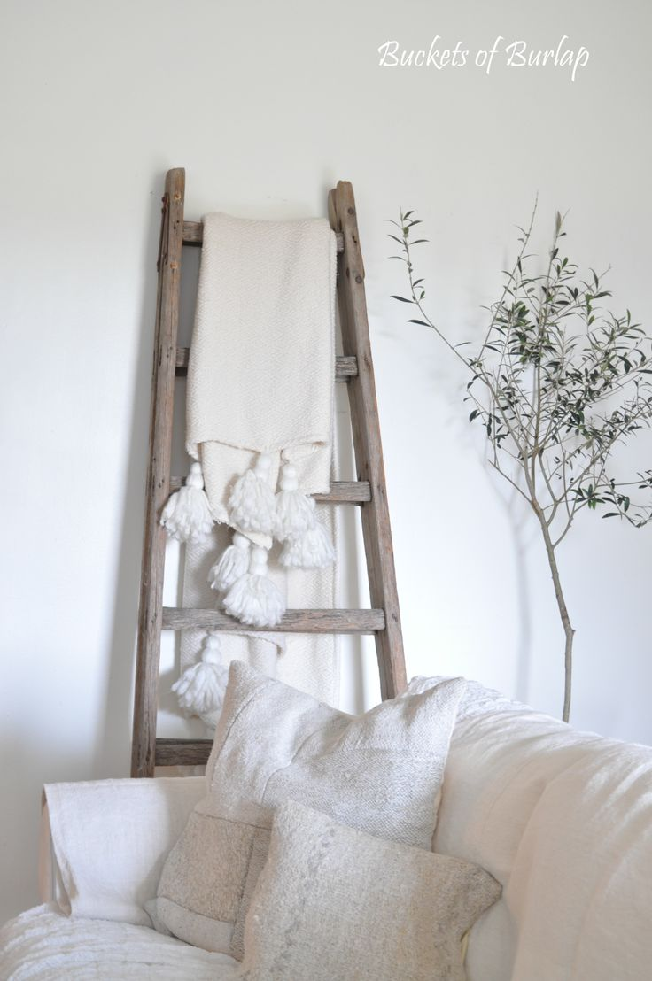 Vintage ladder with Anthropologie tassel throw, olive tree in a French harvest basket, and hemp linen patchwork pillows. Buckets of Burlap blog