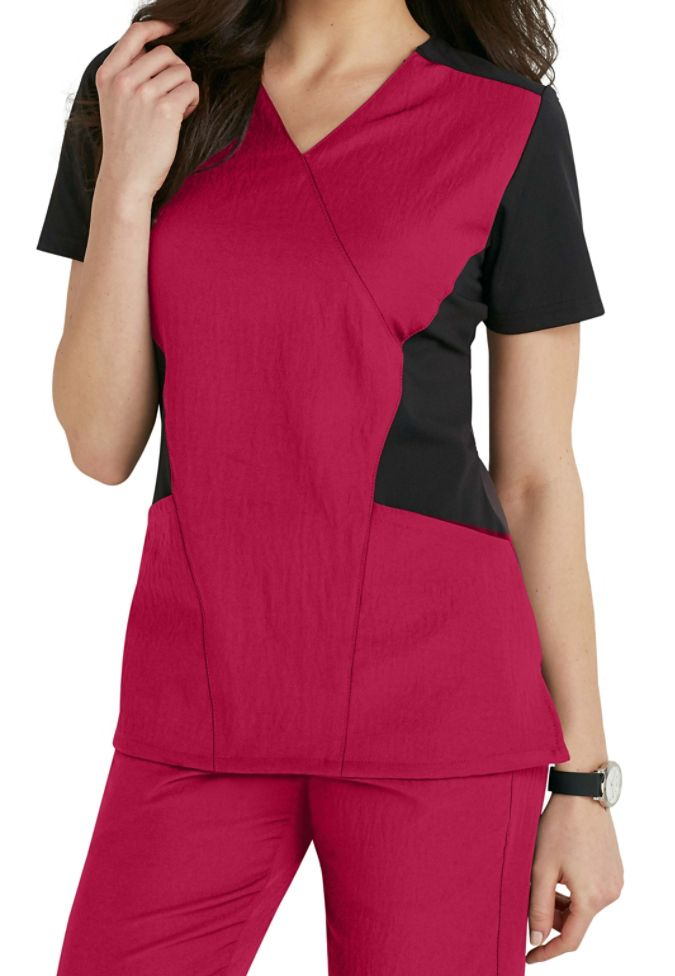 he WonderWink 4-Stretch FFX Sport mock wrap scrub top (in Strawberry) puts an amazing twist on the normal scrub top! This athletically inspired racerback top is designed like active wear and is made with knit side panels for a flattering look. Two top loading pockets and an interior cell phone pocket allow you plenty of space to hold your accessories.