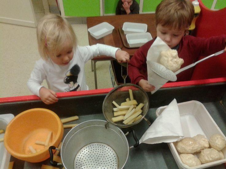 De kindjes spelen van oliebollen en frietkraam in de ontdekbak.