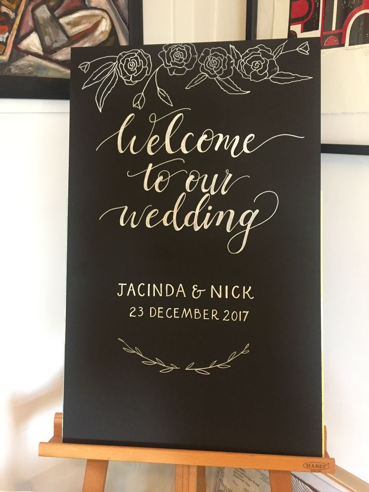 White handwritten calligraphy on black board with floral detail - welcome your guests with pretty detail. Wedding signage at its best.