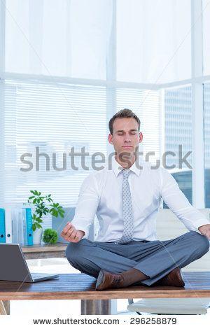 Zen businessman doing yoga meditation on the desk