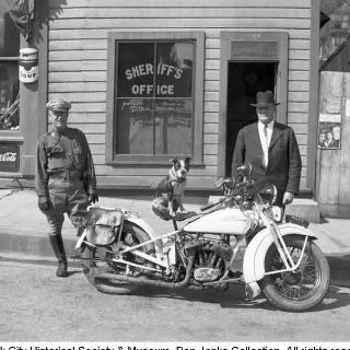 "Title: Officers with dog sitting on motorcycle    Subject:	Law enforcement    Two men, Deputy Sam Billings and Summit County Sheriff Ephraim Adamson, stand facing camera next to white Harley-Davidson motorcycle, with dog named Dodo (who belonged to photographer's daughter, Thelma) sitting on seat looking toward camera. Sheriff's Office at 509 Main St. in background. Signs include Campbell Soup, Coca-Cola & Miracle Man, movie poster. Sign on motorcycle reads: ""SUMMIT COUNTY PATROL.""…"