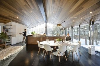 Cupboards rise up the wall to meet the angled ceiling, which itself runs the length of the home