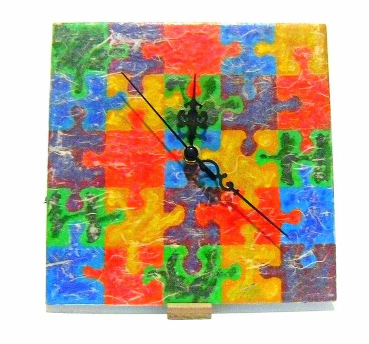 Questo orologio di eco design rappresenta un'altra delle nostre creazioni tese a valorizzare lo scarto fino al punto di concedergli una nuova vita estetica e funzionale. Abbiamo elaborato un motivo decorativo che rimanda direttamente al mondo dell'infanzia  e lo abbiamo riprodotto su una piastrella. L'elemento delle lancette ha concesso di ottenere un totale cambiamento di funzione e quindi un orologio da tavolo.