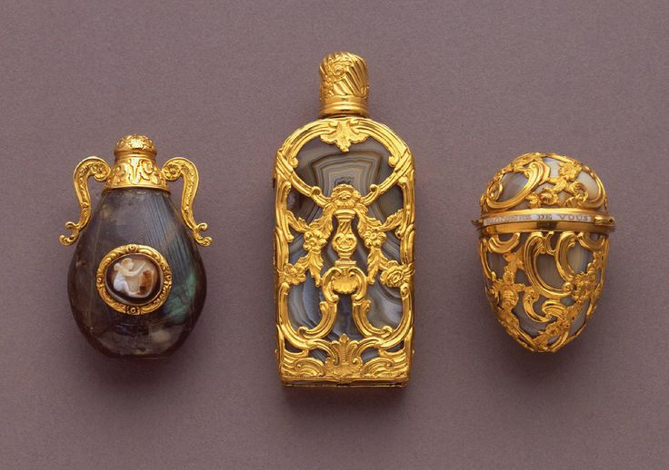 "(L) Bottle, early 18th century, Labradorite, gold, carved stone cameos.   (Center) Perfume bottle, ca. 1750, Agate, gold. United Kingdom.  (R) Bonbonniere, ca. 1750  curving rococo gold cage work over gray agate. Hinged lid with white enamelled band showing the phrase, ""Eloignez de vous rien n'est agreable"" (Separated from you nothing is pleasant) (c) cooperhewitt.org"