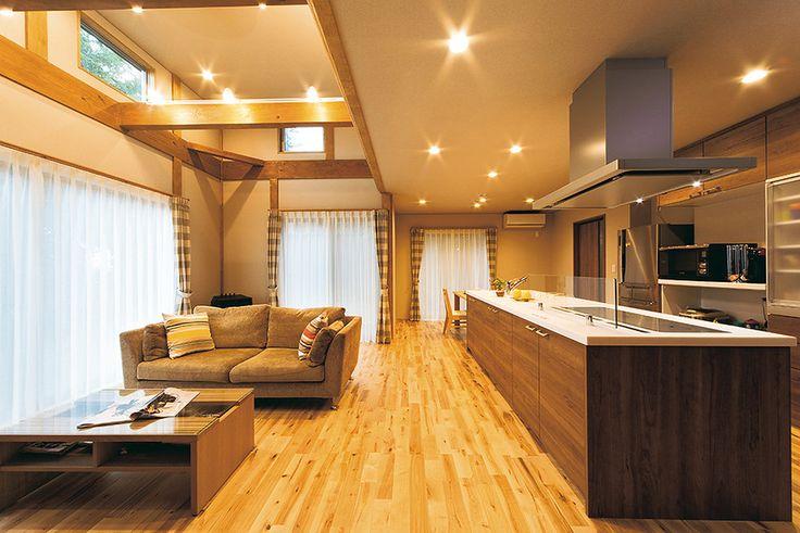 アイランド型キッチンは3つ口のIHクッキングヒーターや食器洗い乾燥機を装備。左手のリビングは梁見せの構造で、奥にペレットストーブを配置。