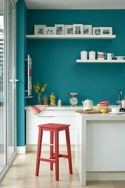 Bright teal walls look great against white gloss kitchen cabinets, and the accent of red further lifts the rich colour.