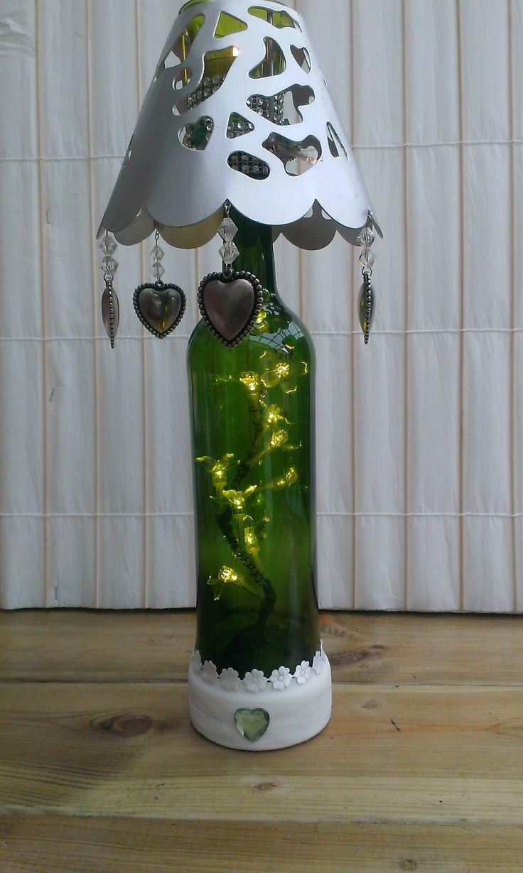 Decoratieve wijnfles met lichtjes erin,en boven in het kapje een theelichtje.