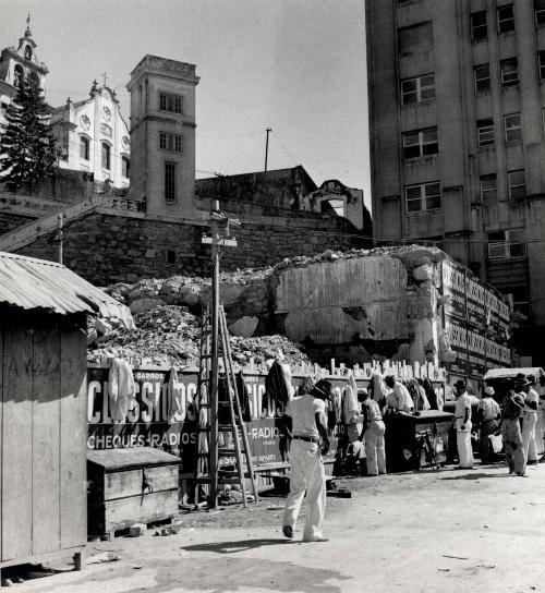 Foto de Genevieve Naylor mostrando um aspecto do Largo da Carioca em 1941. Esta foto serve para lembrar o velho hábito dos trabalhadores do Rio de pendurarem seus paletós num lugar qualquer enquanto trabalhavam. Hoje em dia nenhum deles usa paletó.