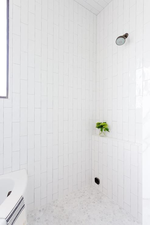 Clad in white vertical wall tiles, this gorgeous walk-in shower features an oil rubbed bronze shower head fixed above a tiled ledge and white mosaic marble floor tiles.
