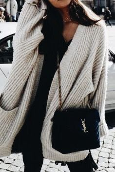 Cozy white knit cardigan over all black with chic handbag.