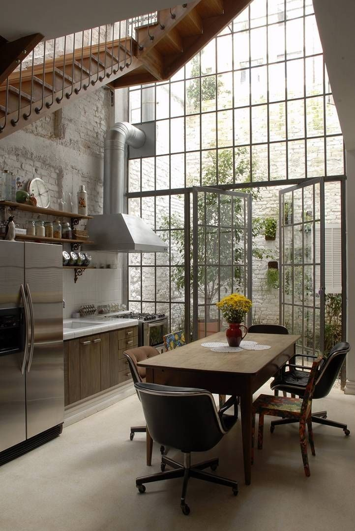 factory-metal-windows-garden-estudio-vitorpenha-gardenista. Two-story factory windows and French doors bring sunlight into a kitchen by Brazil-based Estudio Vitor Penha. WOW!!!