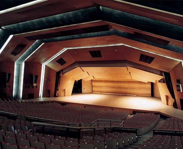 群馬音楽センター 1961年竣工。設計:アントニン・レーモンド。戦前より親交のあった高崎の名士、井上房一郎の依頼により設計。建設資金の3分の1は市民からの寄付でまかなわれたという。壁や天井を蛇腹に折ることで、無柱の大空間を生み出す折板構造を採用。コンクリートの使用量が少なく経済的だということも、採用理由のひとつだった。折板のアーチがそのまま表れた内部は、観客と演者が一体となるよう、またホール自体が楽器のように鳴り響くよう、間口22mの舞台と約2,000ある客席が同一面上で連続する構成がとられている。最大60mものスパンを持ちながら、屋根の厚さはわずか12cmという構造にも驚く。構造計算は後年、〈香川県立体育館〉のそれを手がけた岡本剛が担当した。ガラス張りの開放的なホワイエに設えられた階段や、レーモンド夫妻が描いた壁画なども見どころだ。