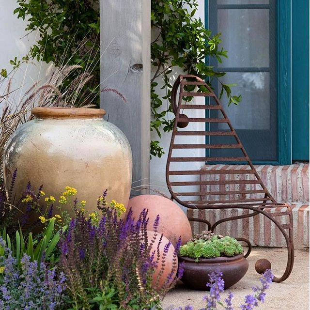 A large oversized pot & other garden elements, along with a unique industrial styled garden chair and brightly colored plants & vines, are a great formula for this stunning patio garden design as posted & shot by #MaggieGrace, #HGTV via #Pinterest. Such a relaxing & gorgeous outdoor living environment.  #patios #patiogarden #flowers #textures #brightcolors #draughtresistant #vines #gardensofinstagram #gardeners #gardenstyle #gardenstyling #gardendesign #gardenelements #pots  #structure…