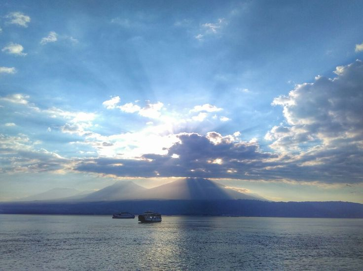 The boat, sea, mountain, and sun ray behind the clouds