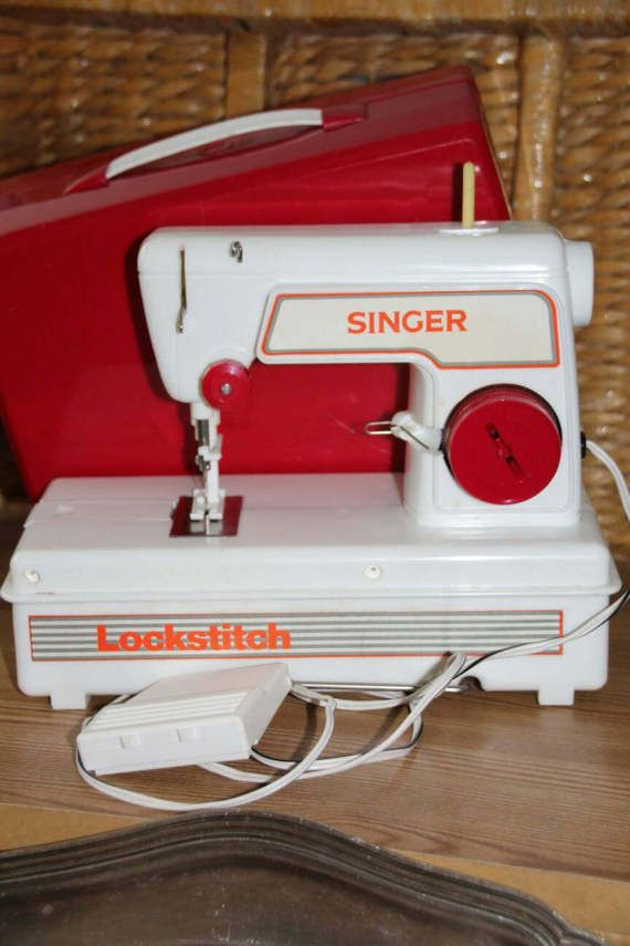 Vintage Lockstitch childs Singer sewing machine with red plastic cover and foot pedal. Good working order. Takes 4 D cell batteries
