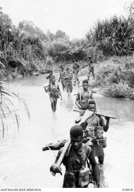 New Guinea. July 1945. Native troops of the New Guinea Infantry Battalion (NGIB) wade a small stream on their way to attack the village of Gisananbu, a Japanese position.