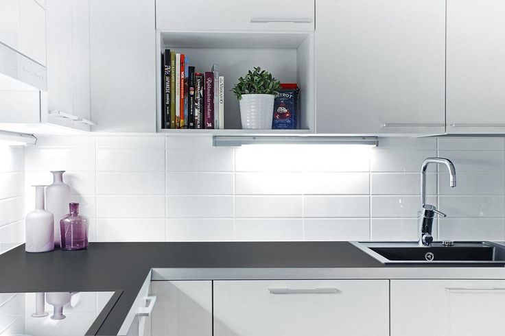 Hladké bílé skříňky s jednoduchými úchyty doplňuje pracovní deska v antracitové barvě.