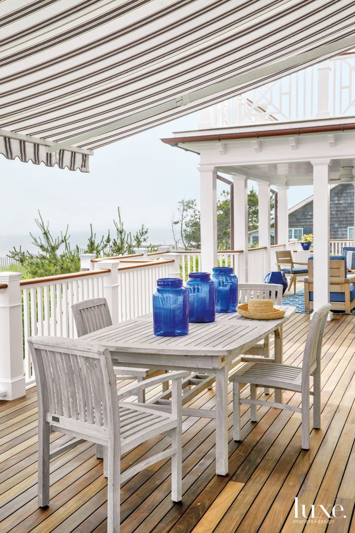 A porch runs along the width of the house, allowing for taking in views of the ocean. In one seating area under an awning, the clients' own table and chairs offer a casual dining experience. The cobalt glass jars, which reference the color palette indoors, are from Nellie's of Amagansett.