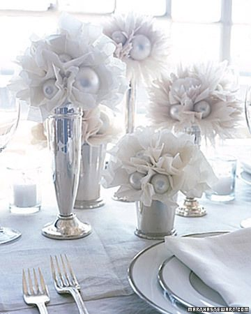 Lush tissue-paper flowers with silver centers arranged at different heights in silver trumpet vases and mint julep cups add a touch of whimsy to a formal reception table