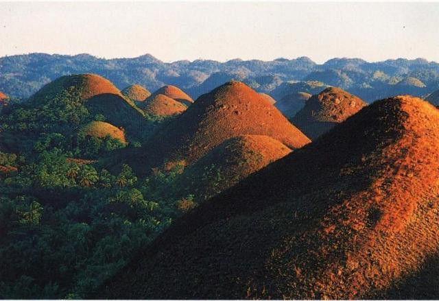 Шоколадные холмы, Филиппины  На обычном плоском пейзаже вдруг поднимаются конические Шоколадные холмы, похожие на конфеты. Во время сезона дождей они покрыты свежим ковром зеленой травы, которая выглядит как мох.