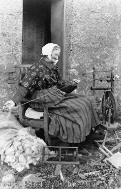 Woman Spinning - notice the pile of fleece to the left and the hand cards on the ground to the right of her wheel.  In the center is her Lazy Kate which holds the bobbins for plying the singles together.