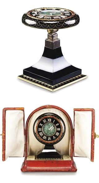 AN ART DECO ENAMEL, JADEITE AND DIAMOND DESK CLOCK, BY CARTIER The pivoting circular dial, set with a carved jadeite panel and diamond-set foliate hands, within an onyx frame applied with diamond Roman numerals, decorated with a French-cut citrine outer frame, to the black enamel case with gold scallop motifs, hinged on an onyx pedestal with geometric details, mechanical movement signed Longines, circa 1925.
