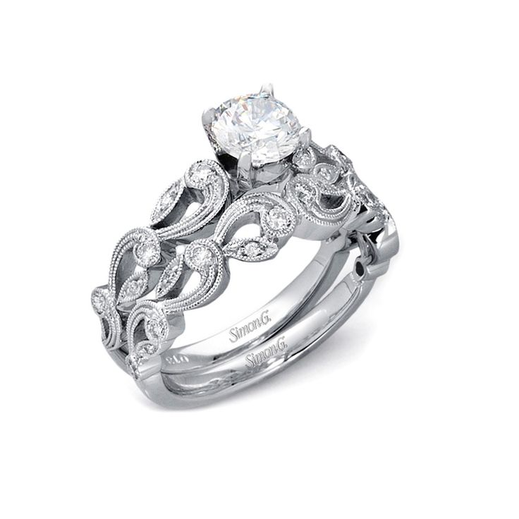 NEW: Beautiful in every way, this vintage inspired Simon G bridal ring set is delicately crafted in 18k white gold and set with round brilliant white diamonds surrounded by fine caviar beading.