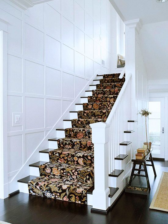 Stylish Staircase Here the crisp white newel post and balustrade, dark wood treads, and a tapestry-look runner combine to make an elegant focal point. The straight geometry of the stairs is echoed in the square paneling on the nearby wall. Repeating patterns adds unity to a room's design
