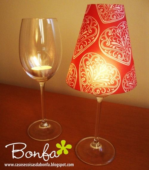 Cheap wine glass + tea light candle + paper cup with bottom cut out.    Wonder if this would work with a cone made from scrap paper!   Would be a great decoration at a party ~ change it for the season/event.