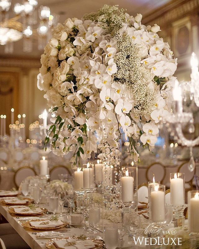 Love the tall white orchid centerpieces with tons of white ...