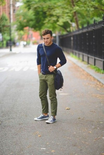 Shop this look on Lookastic:  http://lookastic.com/men/looks/navy-long-sleeve-t-shirt-navy-messenger-bag-olive-chinos-navy-and-white-low-top-sneakers/8074  — Navy Long Sleeve T-Shirt  — Navy Canvas Messenger Bag  — Olive Chinos  — Navy and White Low Top Sneakers