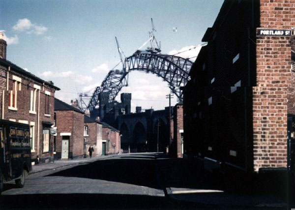 Construction of Runcorn - Widnes road bridge, 1960's Off Portland Street, John Turner & Sons delivery van to the left, view of the bridge during construction and nearing development