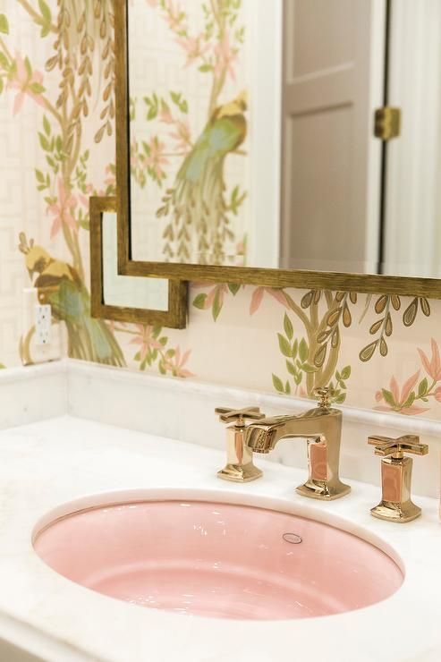 Clad in Nina Campbell Paradiso Wallpaper, this green and pink girl's bathroom features a white marble vanity top fitted with a pink oval sink paired with a brass faucet kit positioned in front of a white marble backsplash located beneath a brass vanity mirror.