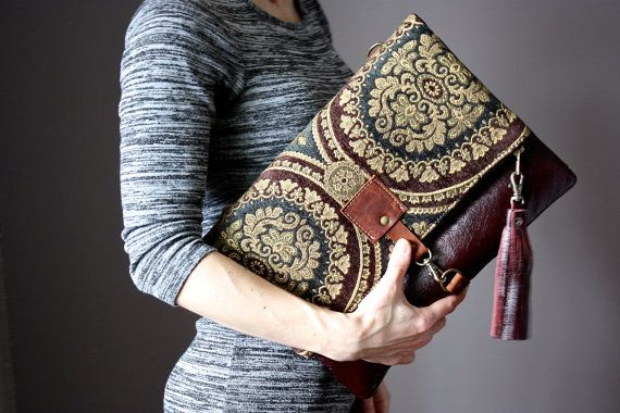 Fold over Clutch bag is made with a genuine cowhide and a gorgeous tapestry fabric. The clutch closes with a metal zipper and a trigger snap hook