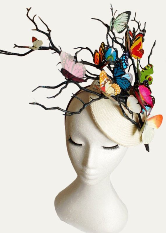 Bespoke hat made with an ivory white sinamay button shape base and multi colour butterflies fluttering about on dark twisted branches. The hat base measures 16cm in diameter. Made to Order. Please let me know the date you need it by. The photos show hats created for different