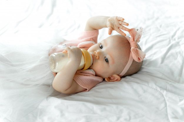 Download Baby Drinks Milk From A Bottle On A White Bed For Free